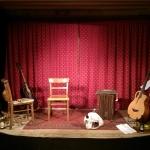Bühne der Liedermacherlounge, roter Vorhang im Hintergrund; auf der Bühne stehen zwei Gitarren im Gitarrenstände,r zwei Sessel und ein Cajon