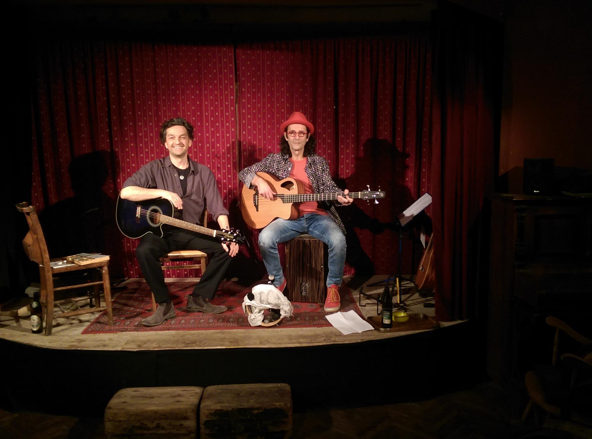 Reinauer im Duo mit Dixi auf der Bühne der Liedermacherlounge, Reinauer links sitzend mit Gitarre, Dixi rechts sitzend mit akustischem Bass