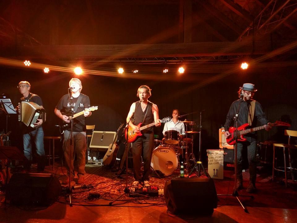 Bild der REINAUERAG live soielend,Bild ist in rotbraunes Licht gehalten, von linls nach rechts Stefan Wackerle an der Ziehharmonika, Hari Hittinger an der Gitarre und Mikro, REINAUER an der Gitarre und Mikro, Jens Gerö am Schlagzeug, Dixi am Bass