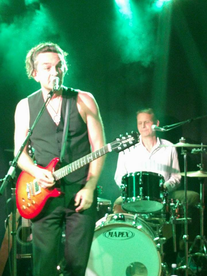 In grünes Licht getauchtes Foto, REINAUER im Vordergrund mit E-Gitarre singt ins Mikrofon, im Hintergrund Jens Gerö am Schlagzeug